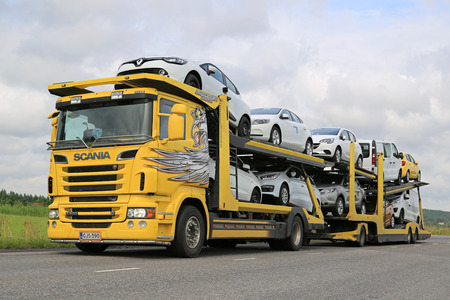 SALO, FINLAND - JULY 26, 2015: Scania R500 car carrier hauls new cars along road. A scrapping scheme for old vehicles will be carried out in Finland between 1 July and 31 December 2015.
