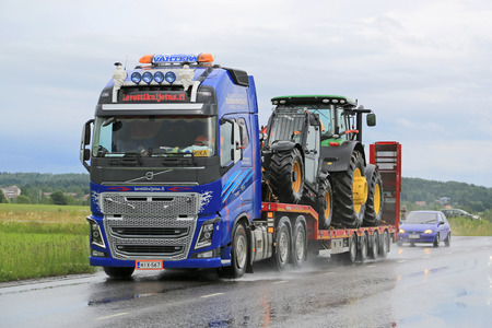 deere: SALO, FINLAND - JULY 10, 2015: Volvo FH16 hauls John Deere machinery on gooseneck trailer. Volvo Trucks certify all engines for the diesel HVO. Editorial