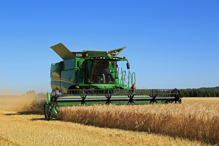 salo: SALO, FINLAND - AUGUST 22, 2015: John Deere Combine s670i harvests barley at Puontin Peltopaivat Agricultural Harvesting and Cultivating Show.