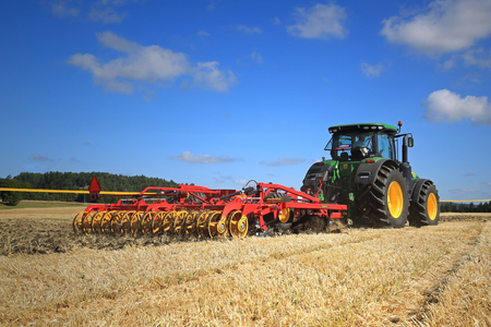 john deere: SALO, FINLAND - AUGUST 22, 2015: John Deere 8370R tractor and Vaderstad Opus 400 cultivator on field at Puontin Peltopaivat Agricultural Harvesting and Cultivating Show.