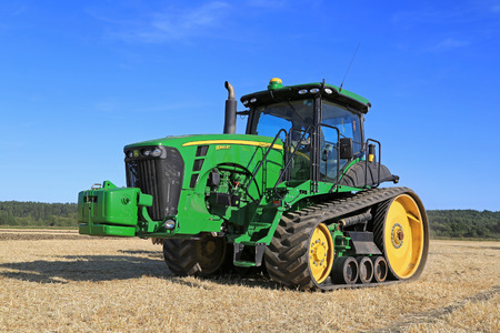 deere: SALO, FINLAND - AUGUST 21, 2015: Unnamed farmer operates John Deere 8345RT tracked tractor on field at setting up of Puontin Peltopaivat Agricultural Harvesting and Cultivating Show. Editorial