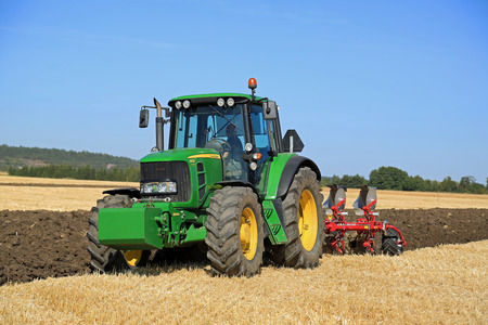 deere: SALO, FINLAND - AUGUST 21, 2015: Unnamed farmer operates John Deere 6630 tractor and Agrolux plow on field at setting up of Puontin Peltopaivat Agricultural Harvesting and Cultivating Show. Editorial