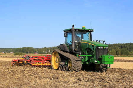 salo: SALO, FINLAND - AUGUST 21, 2015: Unnamed farmer cultivates the field with John Deere 8345RT tracked tractor and Vaderstad cultivator at setting up of Puontin Peltopaivat Agricultural Harvesting and Cultivating Show.