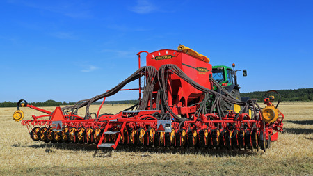 john deere: SALO, FINLAND - AUGUST 21, 2015: Vaderstad Spirit 600C Seed Drill and John Deere 7340 tractor on field at the set up of Puontin Peltopaivat Agricultural Harvesting and Cultivating Show.