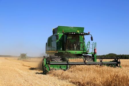 SALO, FINLAND - AUGUST 22, 2015: Two John Deere Combines T550 and s670i harvest barley at Puontin Peltopaivat Agricultural Harvesting and Cultivating Show. Sajtókép