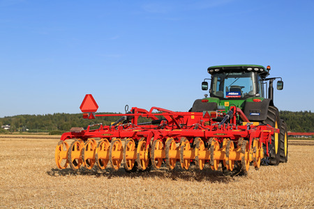 john deere: SALO, FINLAND - AUGUST 21, 2015: New Vaderstad Opus 400 cultivator and John Deere tractor on field at the set up of Puontin Peltopaivat Agricultural Harvesting and Cultivating Show. Editorial