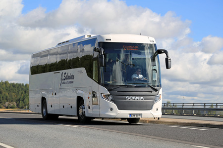 buses: SALO, FINLAND - AUGUST 29, 2015: White Scania Touring coach bus on the road in Salo. The Scania Touring is a tourist coach with Chinese-build Higer bodywork.