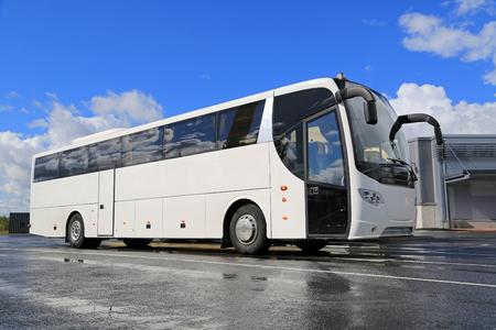 transportation: Bianco pullman attende per i passeggeri alla fermata dell'autobus in una giornata estiva con asfalto bagnato riflettente e cielo blu con nuvole. Archivio Fotografico