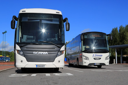 charter: SALO, FINLAND - AUGUST 29, 2015: White Scania Touring and VDL Futura coach bus on the bus stop in Salo. The Scania Touring is a tourist coach with Chinese-build Higer bodywork. Editorial