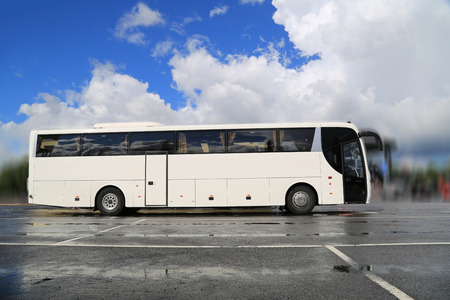 coach bus: White coach bus waits for passengers on a foggy morning after rain. Stock Photo