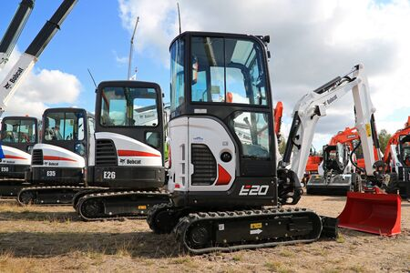 compact track loader: HYVINKAA, FINLAND - SEPTEMBER 11, 2015: Lineup of Bobcat compact excavators with E20 on the front on display at MAXPO 2015.