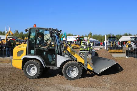 wheel loader: HYVINKAA, FINLAND - SEPTEMBER 11, 2015: Unnamed man demonstrates Kramer Allrad 350 compact wheel loader at MAXPO 2015.