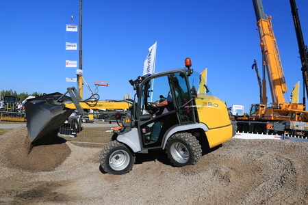 unnamed: HYVINKAA, FINLAND - SEPTEMBER 11, 2015: Unnamed man demonstrates work with Kramer Allrad 350 compact wheel loader at MAXPO 2015.