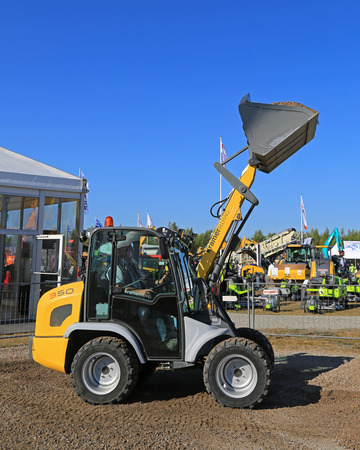 unnamed: HYVINKAA, FINLAND - SEPTEMBER 11, 2015: Unnamed man demonstrates Kramer Allrad 350 compact wheel loader at MAXPO 2015.