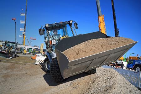 wheel loader: HYVINKAA, FINLAND - SEPTEMBER 11, 2015: Unnamed man demonstrates work with Kramer Allrad 350 compact wheel loader at MAXPO 2015.