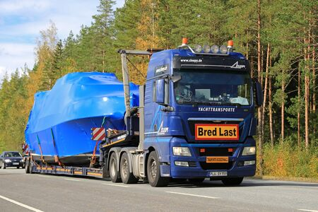 exceptional: TAMMELA, FINLAND - SEPTEMBER 19, 2015: MAN truck hauls a boat as exceptional load along highway.  Abnormal transport permit is required, if any dimension of the transport exceeds the free dimension limits.