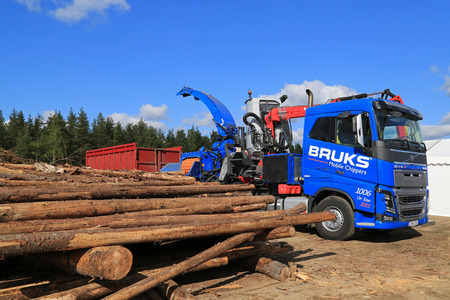 logging truck: HYVINKAA, FINLAND - SEPTEMBER 11, 2015: Tree trunks and equipment for making woodchip mounted on blue Volvo FH16 750 woodchip truck on display at MAXPO 2015.