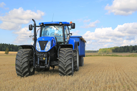 decades: SOMERO, FINLAND - SEPTEMBER 12, 2015: New Holland T7.250 Tractor and blue agricultural trailer on stubble field. New Holland celebrates 12 decades of innovation in 2015.