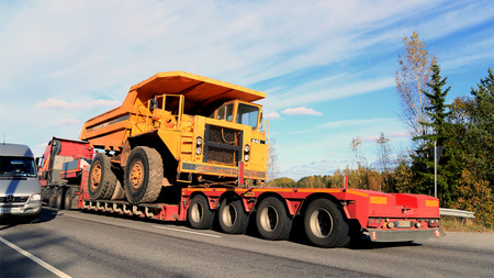 PARAINEN, FINLAND - OCTOBER 9, 2015: Volvo FH hauls a Volvo BM 540 Rigid dump truck as wide load. The BM 540 was designed a cost-effective load carrier for construction and mining. Editorial