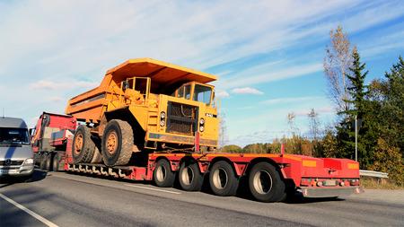 Parainen, FINLANDIA - 9 de octubre de 2015: Volvo FH transporta un camión volquete rígido Volvo BM 540 de carga como de ancho. El BM 540 se diseñó un vehículo de carga rentable para la construcción y la minería. Editorial