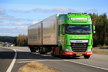 introduces: SALO, FINLAND - OCTOBER 9, 2015: Lime green DAF XF full trailer truck on motorway. DAF introduces new products at Amsterdam RAI show in October 2015.