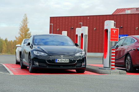 supercharger: TOIJALA, FINLAND - OCTOBER 17, 2015: Three Tesla Model S cars are being charged at Tesla Supercharger station. Currently there are two Tesla Supercharger stations in Finland.