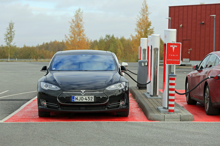 supercharger: TOIJALA, FINLAND - OCTOBER 17, 2015: Three Tesla Model S cars are plugged in at Tesla Supercharger station. Supercharging is free for the life of Model S.