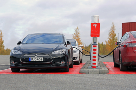 plugged in: TOIJALA, FINLAND - OCTOBER 17, 2015: Three Tesla Model S cars are plugged in at Tesla Supercharger station. Supercharging is free for the life of Model S.