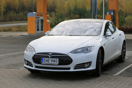 electric current: TOIJALA, FINLAND - OCTOBER 17, 2015: White Tesla Model S Electric Car parked close to Tesla Supercharger Point. The current two Tesla Supercharger stations in Finland are located in Toijala and Paimio. Editorial