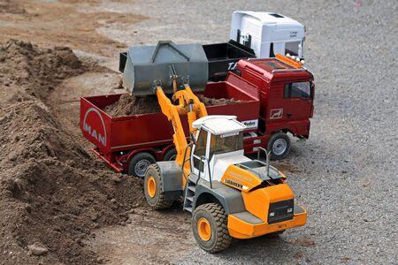 wheel loader: ALAHARMA, FINLAND - AUGUST 8, 2015: Liebherr 2plus2 L574 Wheel Loader unloads sand on MAN Tipper truck. Also RC model vehicles were presented at Power Truck Show.