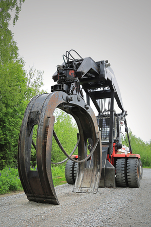 grapple: AANEKOSKI, FINLAND - JUNE 20, 2015: Svetruck TMF 25-18 logstacker on a yard at Midsummer. This forest industry logstacker has a grapple of 7,5 m2 for unloading lorries or railway wagons.