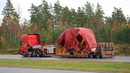 exceeds: PAIMIO, FINLAND - OCTOBER 23, 2015: Scania R730 truck hauls industrial object covered with tarpaulin as exceptional load. Abnormal transport permit is required, if any dimension of the transport exceeds the free dimension limits.