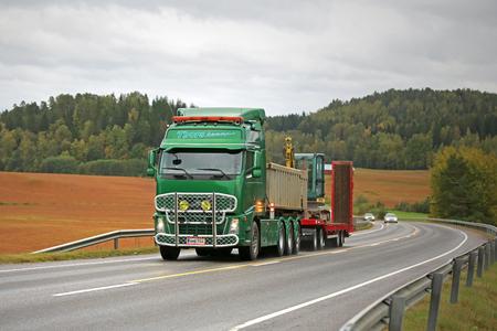 SALO, FINLAND - SEPTEMBER 18, 2015: Green Volvo FH hauls Yanmar Vio 57 Mini excavator. Vio 57 has a horizontal reach of 4,32 m and dredging depth of 3,73 m. Editorial