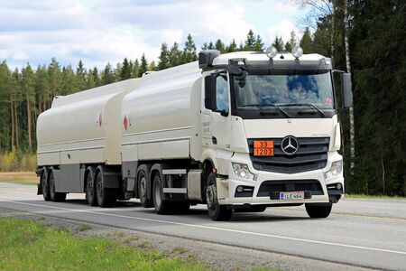 signifies: FORSSA, FINLAND - MAY 16, 2015: White Mercedes-Benz Actros 2545 tank truck on the road. The ADR code 33-1203 signifies petrol fuel.