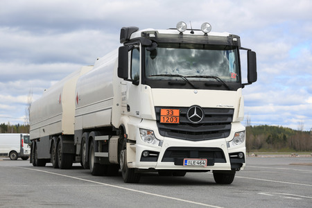 signifies: FORSSA, FINLAND - MAY 16, 2015: White Mercedes-Benz Actros 2545 tank truck parked on a yard. The ADR code 33-1203 signifies petrol fuel.
