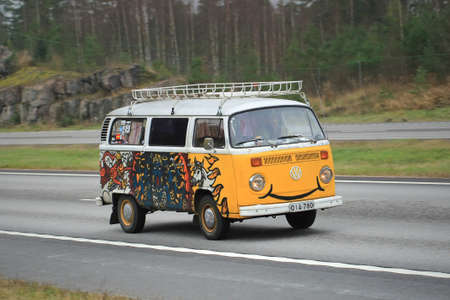 automaker: PAIMIO, FINLAND – NOVEMBER 1, 2015: Painted Volkswagen Type 2 Camper Van on motorway in South of Finland. The Type 2 was first introduced in 1950 by the German automaker Volkswagen.