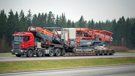 Paimio, Finland - 1 november 2015: Scania R620 Semi uitzettingen Sandvik US440i Mobile Cone Crusher. De heavy duty kegelbreker is ontworpen voor de behoeften van grote mijn of steengroeve operators.