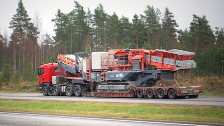 oversize load: PAIMIO, FINLAND - NOVEMBER 1, 2015: Scania R620 Semi hauls Sandvik US440i Mobile Cone Crusher. The heavy duty cone crusher is designed for the needs of large mine or quarry operators.