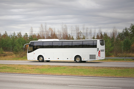 coach bus: New white coach bus moves along motorway on a cloudy autumn day.