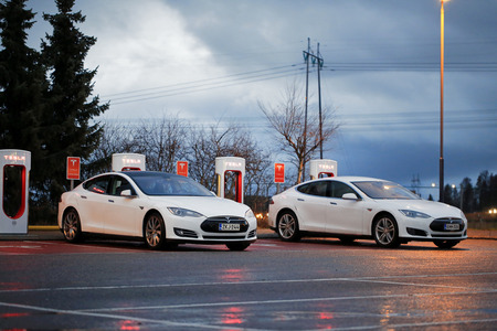 supercharger: PAIMIO, FINLAND - OCTOBER 17, 2015: Two white Tesla Model S cars are being charged at Tesla Supercharger station at night. Tesla Supercharging stations charge up to 16 times as fast as public charging stations. Editorial