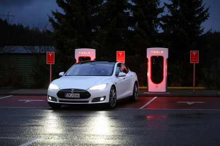 supercharger: PAIMIO, FINLAND - NOVEMBER 14, 2015: Tesla Model S electric car arrives at the Paimio Tesla Supercharger station at night for charging. Tesla Supercharging stations are open any time.