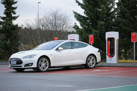 electric current: Paimio, Finland - November 15, 2015: White Tesla Model S electric car being charged at the Paimio Tesla Supercharger station. The Supercharger gives the Model S 270 km of range in about 30 minutes.