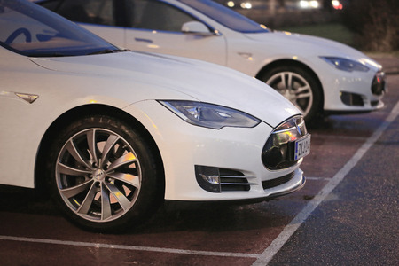 supercharger: PAIMIO, FINLAND - NOVEMBER 14, 2015: Two white Tesla Model S cars are being charged at Tesla Supercharger station at night. Tesla Supercharging are open at any time.