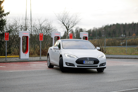 supercharger: Paimio, Finland - November 15, 2015: Tesla Model S electric car leaves the Paimio Tesla Supercharger station. Tesla Supercharger gives the Model S 270 km of range in about 30 minutes. Editorial
