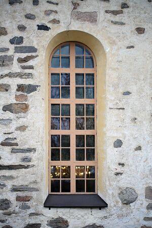 luz de velas: ventana de arco de una iglesia medieval de piedra con la luz de las velas.