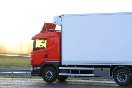 Red de temperatura controlada camión de carga por una parada de camiones está listo para ir por la mañana al amanecer.