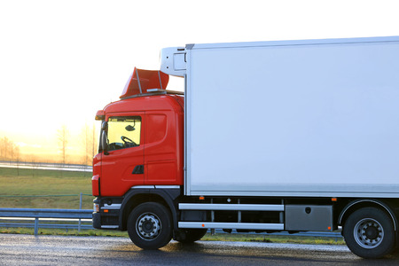reefer: Red temperature controlled cargo truck by a truck stop is ready to go in the morning at sunrise.