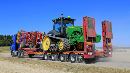 john deere: SALO, FINLAND - AUGUST 22, 2015: Volvo FH hauls John Deere 8345RT tracked tractor and cultivator at the end of Puontin Peltopaivat Agricultural Harvesting and Cultivating Show, public event. Editorial
