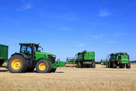 deere: SALO, FINLAND - AUGUST 21, 2015: John Deere 7280R tractor and Combine harvesters on field at the set up of Puontin Peltopaivat Agricultural Harvesting and Cultivating Show, public event.