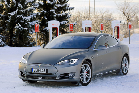 supercharger: PAIMIO, FINLAND - JANUARY 17, 2016: Unidentified man drives Tesla Model S at Supercharger Station Paimio on a cold wintery day. Unlike conventional cars, electric cars will always start in winter.